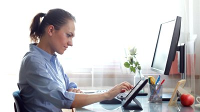 stock-footage-young-businesswoman-working-on-tablet-computer-and-smiling